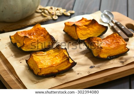 Baked pumpkin pieces with caramelized sugar on top, a traditional autumn snack in Hungary, photographed with natural light (Selective Focus, Focus on the first piece on the left) - stock photo
