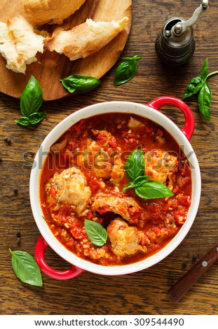 Baked rabbit in tomato sauce with rosemary and basil. Italian Cuisine. - stock photo