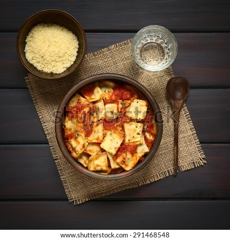 Baked ravioli with homemade tomato sauce in rustic bowl with grated cheese in small bowl, glass of water and wooden spoon on the side, photographed overhead on dark wood with natural light - stock photo
