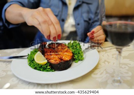 baked red fish with a lemon. The waiter brings the red steak baked salmon