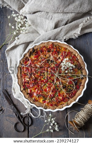 baked red peppers tart on quiche mold on rustic table with cloth, scissor and spool