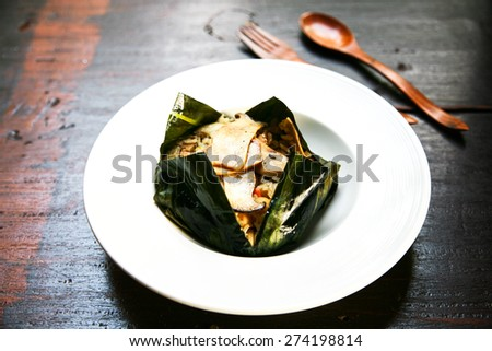 Baked rice with wholegrain   in joist banana leaves, thai's traditional northern food on black wood table / healthy food selective focus - stock photo