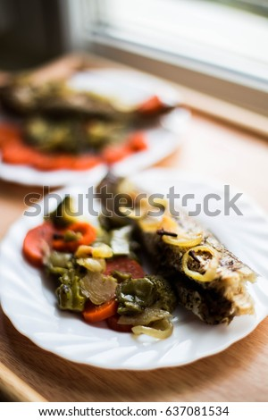 Baked roasted fried fish with baked, baked, gifted vegetables on a wooden table