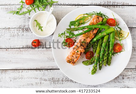 Baked salmon garnished with asparagus and tomatoes with herbs.Top view - stock photo