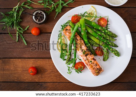 Baked salmon garnished with asparagus and tomatoes with herbs.Top view