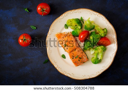 Baked salmon garnished with broccoli and tomato. Top view