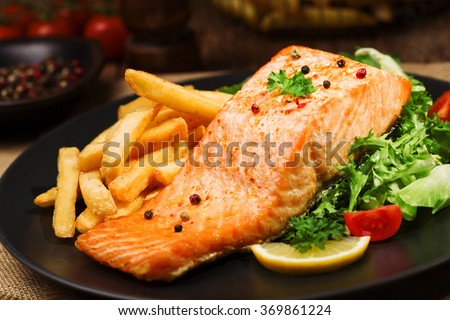 Baked salmon served with french fries and fresh vegetables.   - stock photo
