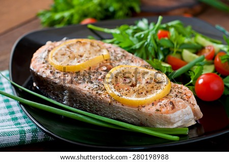 Baked salmon steak with lemon and herbs - stock photo