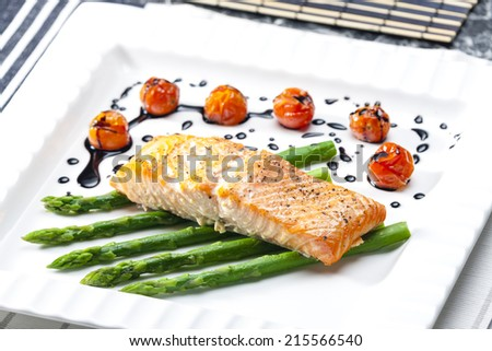 baked salmon with green asparagus and cherry tomatoes - stock photo