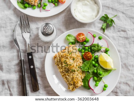 Baked salmon with lemon bread crust and fresh vegetable salad with peas, spinach, radishes and cherry tomatoes. Delicious healthy dinner - stock photo