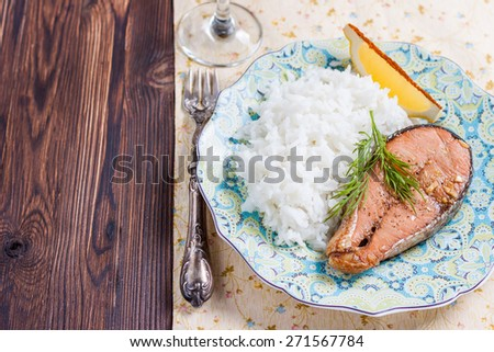 Baked salmon with rice garnish. Plate with grilled salmon, rice, lemon and a glass of wine on the table. Lunch / dinner. Copy space. - stock photo