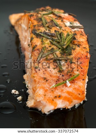 Baked salmon with rosemary shot on a black plate