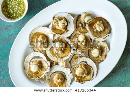 Baked scallops with butter and soy sauce in natural scallop shell delicious Thai sea food. - stock photo