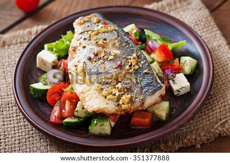 Baked seabass with Greek salad - stock photo