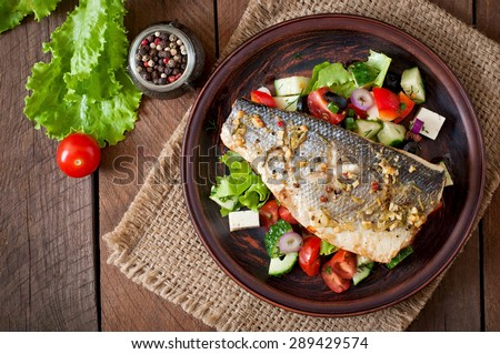 Baked seabass with Greek salad. Top view - stock photo