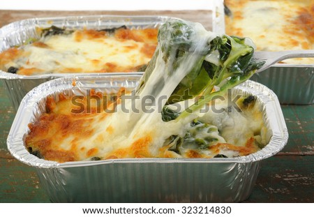 baked spinach with cheese in aluminium foil tray - stock photo