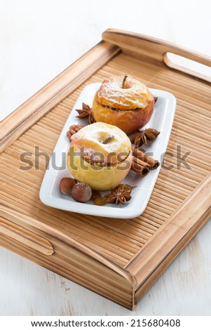 baked stuffed apples on a white plate on wooden tray, vertical - stock photo