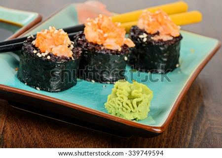 Baked sushi rolls with black rice and salmon, served on blue plate with pickled ginger and chopsticks. - stock photo