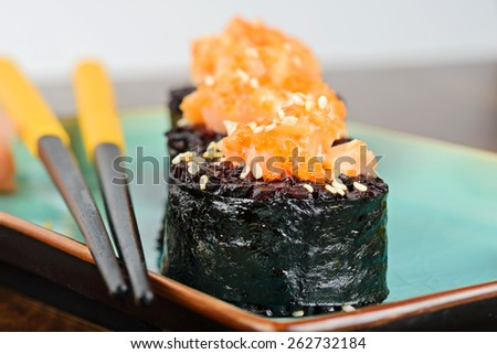 Baked sushi rolls with black rice and salmon, served on turquoise plate and black chopsticks. - stock photo