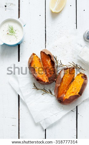 Baked sweet potatoes, dip, salt and rosemary. White wooden rustic picnic table scenery from above.