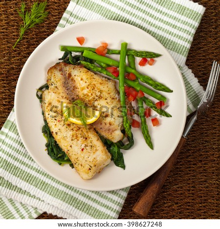 Baked Tilapia Fish Fillet with Asparagus. Selective focus. - stock photo