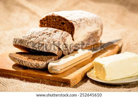 Baked to perfection. Closeup shot of a sliced home-baked bread and a piece of butter with knife on a farm style sackcloth