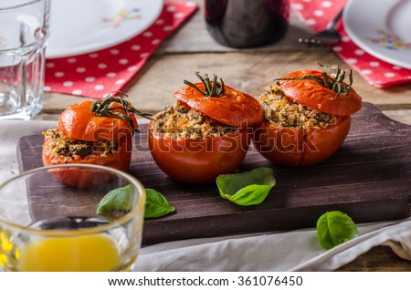 Baked tomatoes stuffed with herbs, delicious vegetarian meal - stock photo