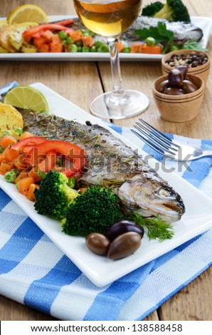 Baked trout vegetables and white wine on the kitchen table - stock photo