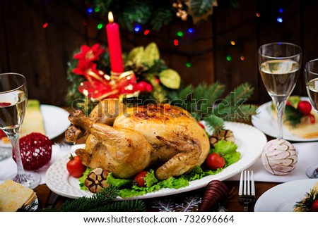 Baked turkey (chicken). The Christmas table is served with a turkey, decorated with bright tinsel and candles. Fried chicken, table. Christmas dinner