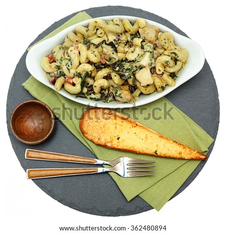 Baked Tuscan Chicken Pasta with Artichoke and Garlic Bread Over White - stock photo