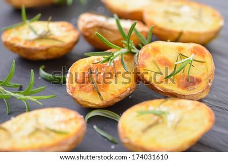 Baked unpeeled potatoes with rosemary - stock photo