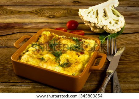 Baked vegetable cauliflower casserole in breadcrumbs with cheese on a square ceramic baking dish, fork, tomatoes, wooden background, vegetable casserole, cauliflower casserole, vegetarian casserole  - stock photo
