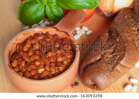 Baked white beans with tomatoes, basil and bread - stock photo