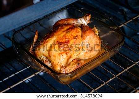 Baked whole chicken in a glass pan in an oven