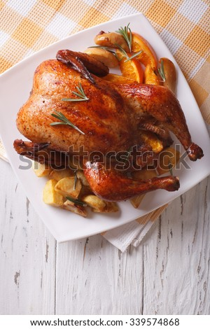 baked whole chicken with oranges and potatoes close-up on a plate. vertical top view