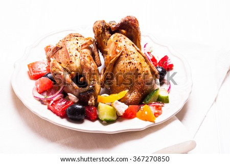Baked whole quail and fresh vegetable salad in white plate on table with green napkin - stock photo
