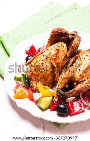 Baked whole quail and fresh vegetable salad in white plate on table with green napkin