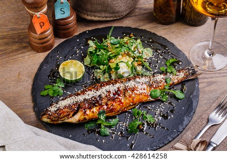baked whole seabass grilled on a plate with vegetables and lemon  for the menu - stock photo