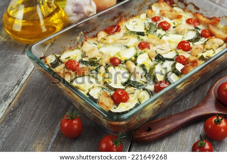 Baked zucchini with chicken, cherry tomatoes and herbs in a glass pot  - stock photo