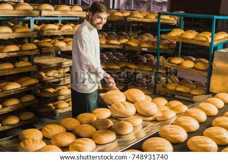 Baker. Bakery. A young handsome worker at a bakery on a background of shelves with spikelets of wheat in his hands. Industrial production of bakery. A man in special clothes of a baker. Working.