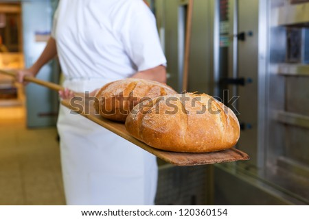 baker baking fresh bread in the bakery showing it on the shovel - stock photo