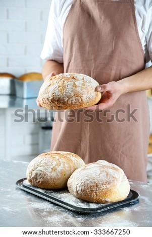 Baker checking freshly baked bread in kitchen of bakery - stock photo
