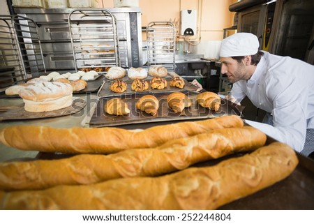 Baker checking freshly baked bread in the kitchen of the bakery - stock photo