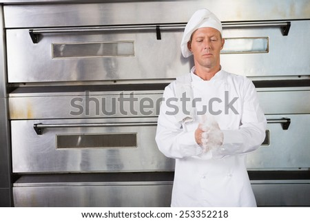 Baker clapping flour from his hands in the kitchen of the bakery