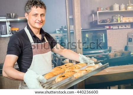baker concept. Happy baker showing tray of fresh bread in the kitchen of the bakery - stock photo