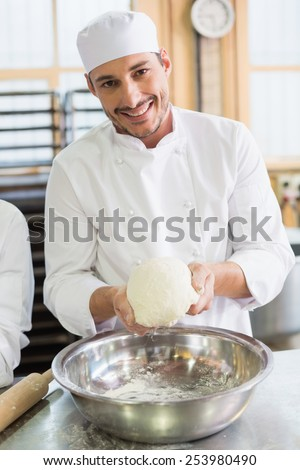 Baker forming dough in mixing bowl in the kitchen of the bakery - stock photo