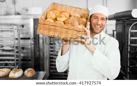 Baker holding basket of bread in the kitchen of the bakery - stock photo