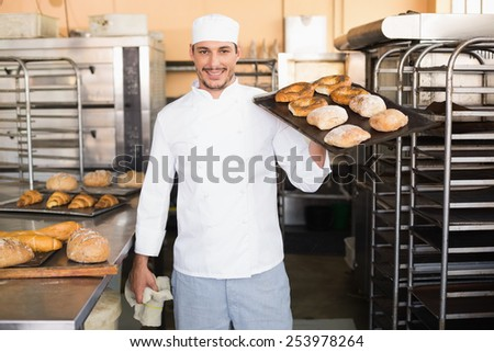Baker holding tray of bread in the kitchen of the bakery - stock photo