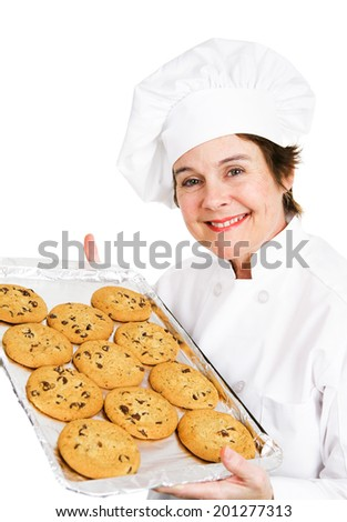Baker holding up a tray of fresh hot chocolate chip cookies.  Isolated on white.