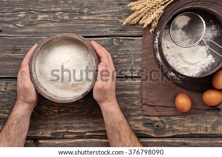 Baker holds a wooden bowl with flour powder on a dark wooden table in a bakery, top view - stock photo
